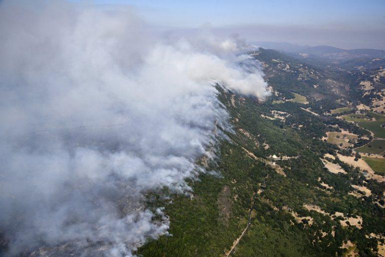 2017年10月9日,野火在加州纳帕东部的山丘燃烧升起烟雾 (图片来源:Michael Short/San Francisco Chronicle via AP)