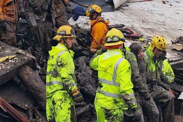 救援人员从齐腰的泥水中救出一名被困的14岁少女。(Mike Eliason/Santa Barbara County Fire Department via AP)