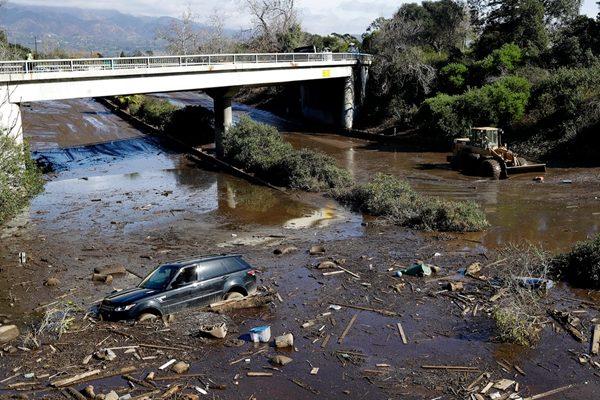 一辆汽车陷在已经变成河流的路上。(AP Photo/Marcio Jose Sanchez)