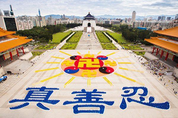11月26日上午,台湾及世界各地的部分法轮功学员约6300人,他们身穿着深黄、浅黄、红、黑、蓝、白色的服饰,在中正纪念堂前排出壮观的「法轮图形」、16道光芒及下方文字「真善忍」。(陈柏州/大纪元)