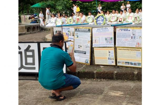公园(Lumphini Park)游客在拍摄法轮功真相展板。(泰国法轮大法佛学会摄)