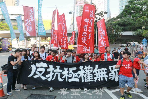 """香港游行队伍中""""反抗极权无罪""""的大型黑色横幅。(摄影:梁路思)"""