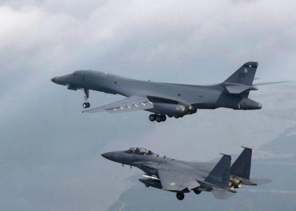 美军在韩半岛部署的军力战力强大,一图为美国B-1B超音速轰炸机(上)和韩国F-15K(下)飞跃韩国乌山空军基地。(AFP)