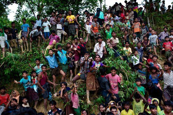 年轻罗兴亚穆斯林在伸手等待分发难民物资。(AP Photo/Bernat Armangue)