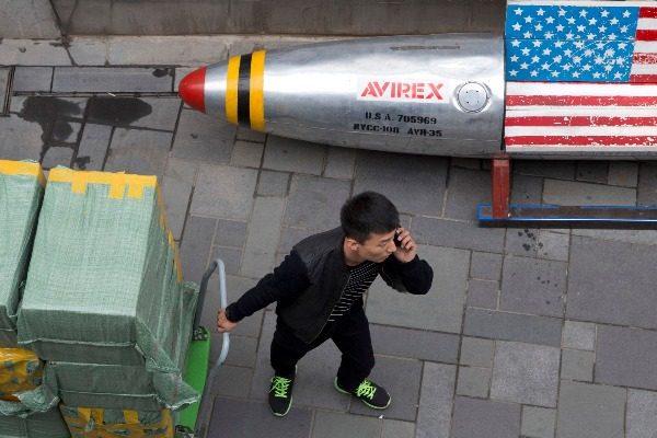 图为一名运货男子经过北京的一家商店(美联社图/AP)