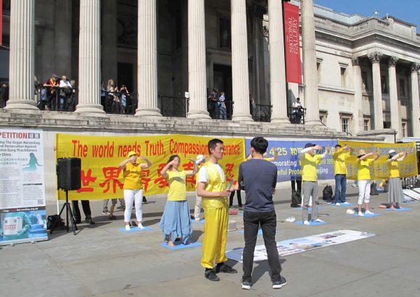"""图1:2019年4月21日,英国法轮功学员纪念""""四·二五""""和平上访二十周年。图为法轮功学员在位于伦敦市中心的特拉法加广场(Trafalgar Square)北平台集体炼功。(minghui)"""