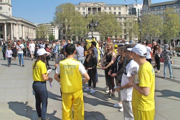"""图3:2019年4月21日,英国法轮功学员纪念""""四·二五""""和平上访二十周年。图为在位于伦敦市中心的特拉法加广场,游客学炼法轮功第二套功法动作,体验到美好的感受。(minghui)"""