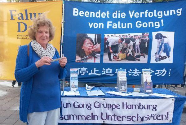 """图4:2019年4月20日,德国汉堡法轮功学员纪念""""四·二五""""和平上访二十周年。退休教师普莱欣(Preising)女士来到法轮功展位,希望迫害马上得以制止。( minghui)"""