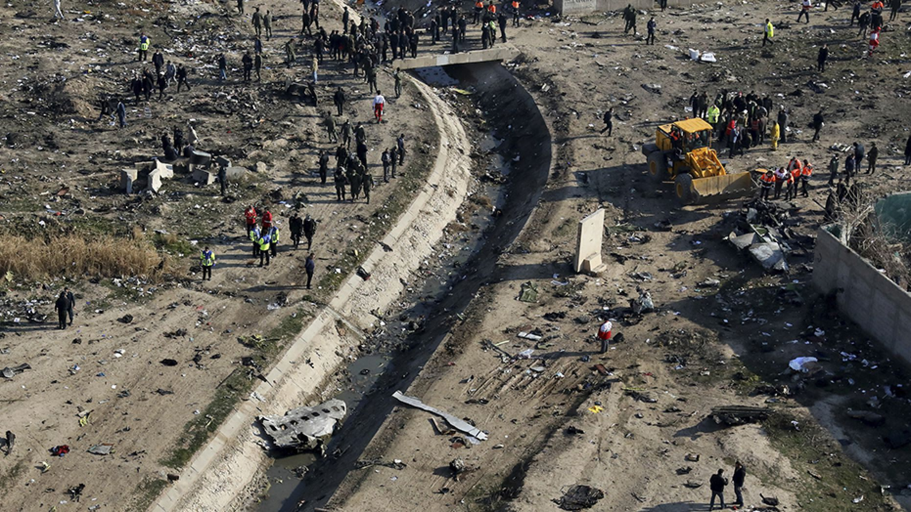 Rescue workers search the scene where an Ukrainian plane crashed in Shahedshahr, southwest of the Iranian capital of Tehran, on Wednesday. (AP)