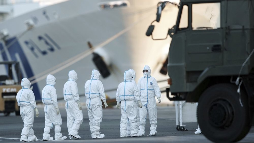 Officials with protective suites prepare work around the quarantined cruise ship Diamond Princess in the Yokohama Port Monday, Feb. 10, 2020, Yokohama, Japan. Japan's health ministry said Monday that about 60 more people on the quarantined cruise ship have tested positive for a new virus. (AP Photo/Eugene Hoshiko)