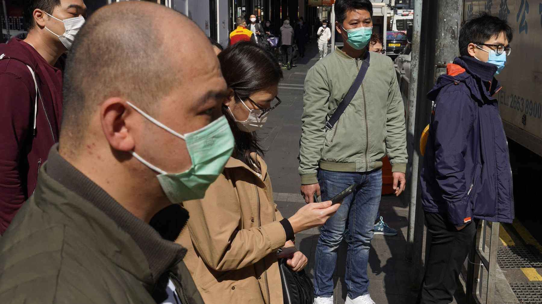 People wearing face masks walk on a down own street in Hong Kong Friday, Feb. 21, 2020. COVID-19 viral illness has sickened tens of thousands of people in China since December. (Associated Press)