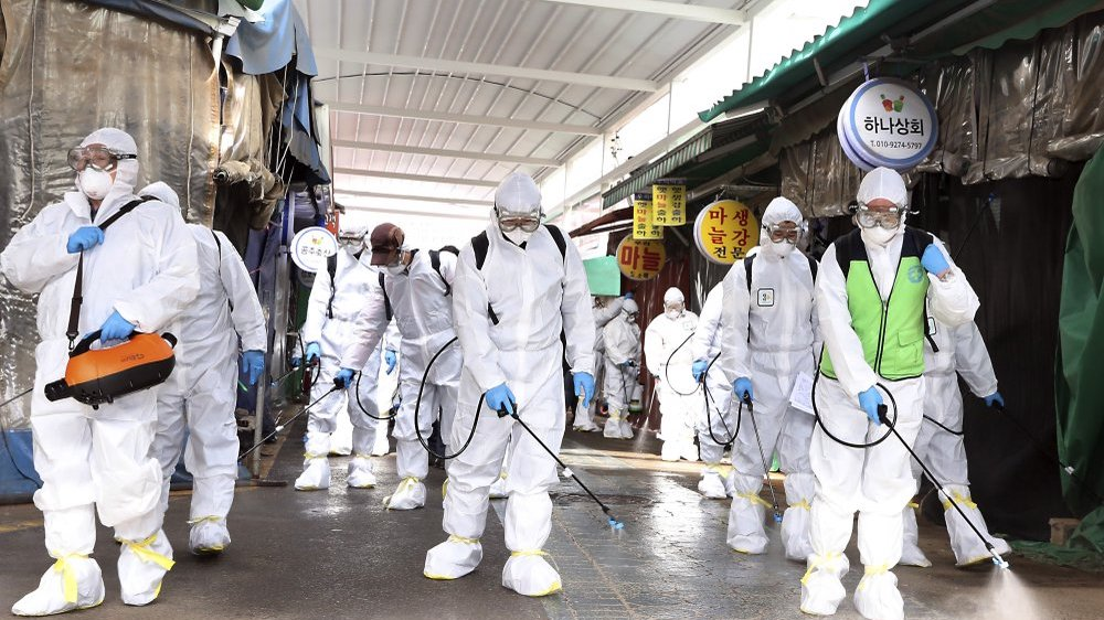 Workers wearing protective suits spray disinfectant as a precaution against the coronavirus at a market in Bupyeong, South Korea, Monday, Feb. 24, 2020.  (Lee Jong-chul/Newsis via AP)