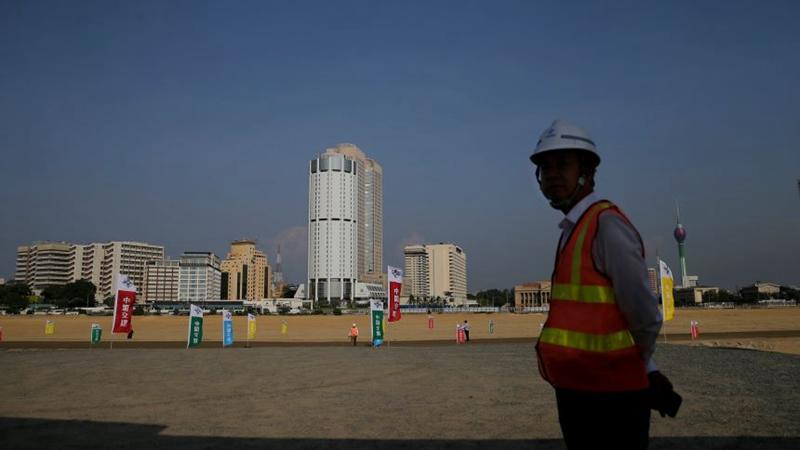 """一名""""一带一路""""建设工人站在阴影下(AP/美联社)"""