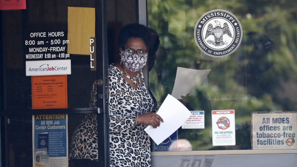 A masked worker at this state WIN job center in Pearl, Miss., holds an unemployment benefit application form as she waits for a client, Tuesday, April 21, 2020.(AP Photo/Rogelio V. Solis)