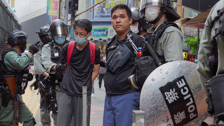 图为,24日香港举行反恶法大游行中,防暴警察抓捕示威者。(美联社)
