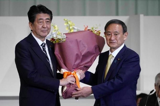 日本首相新任菅义伟(右),左为刚刚卸任的前首相安倍晋三。