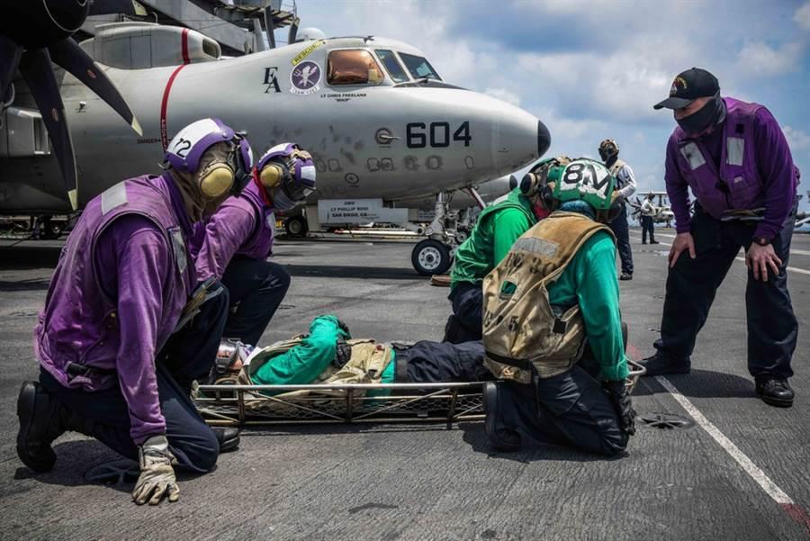 从美国太平洋舰队公布的画面中,可以看到雷根号航母(USS Ronald Reagan CVN-76)的飞行甲板上摆着多具救援器具,扮演「伤者」的航母舰员躺在担架上,其他舰员为这些「伤者」提供转移和救助。