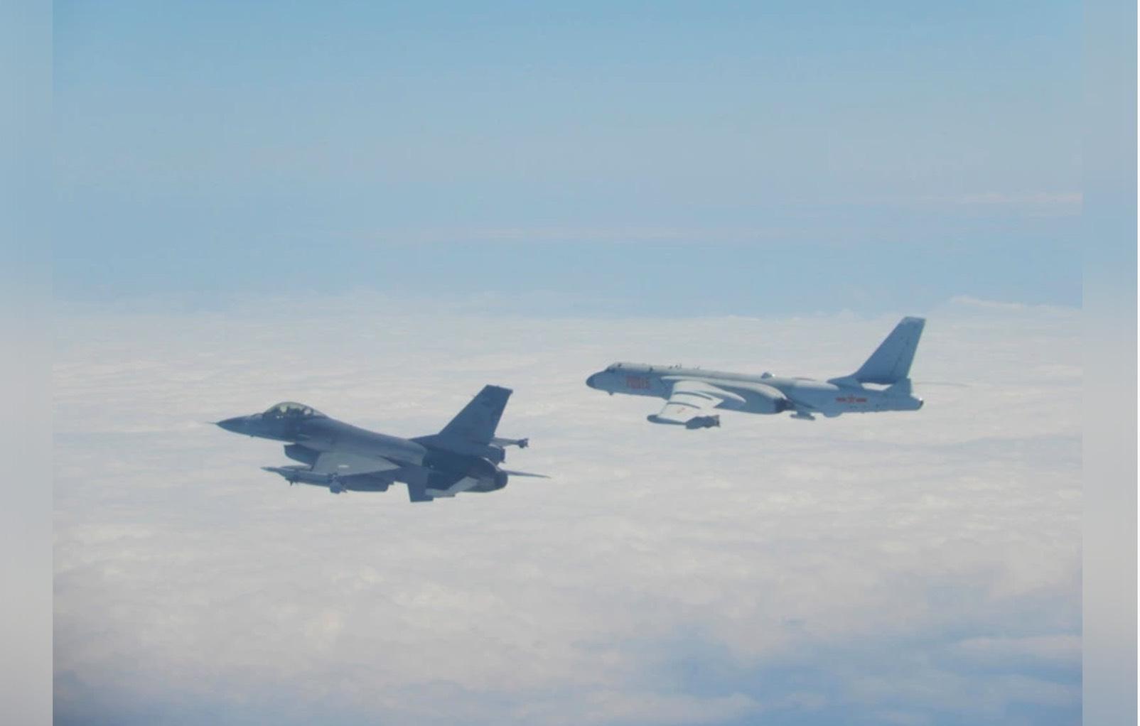 中共军机不断扰台,图为解放军轰6机(右)飞经巴士海峡,国军F-16(左)监控伴飞